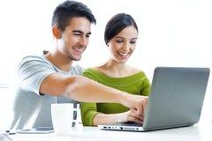 愉快的年轻夫妇浏览互联网在家 库存照片