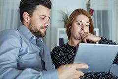 愉快的年轻夫妇用途片剂个人计算机 免版税图库摄影