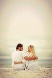 愉快的年轻夫妇由海洋坐海滩 库存图片