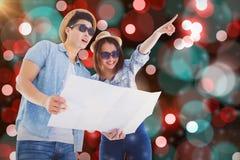 愉快的年轻夫妇的综合图象使用地图的方向的 免版税库存照片