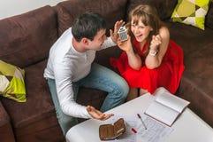 愉快的年轻夫妇计算的家庭预算 图库摄影