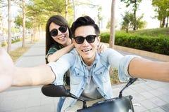 愉快的年轻夫妇骑马滑行车和做selfie照片 免版税库存图片