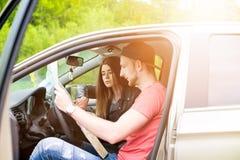 愉快的年轻夫妇,做selfie的朋友,当坐在汽车时 新的成人 白种人人民 背景在飞机运输白色的概念地球 免版税库存图片