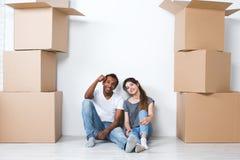 愉快的年轻夫妇画象坐装备的地板看照相机和作他们新的家和 免版税库存图片