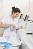 愉快的年轻女性雇员倾吐的洗涤剂在洗衣机洗衣店 库存照片
