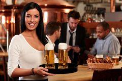 愉快的年轻女服务员用啤酒 免版税库存照片