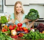 愉快的主妇用未加工的圆白菜在家庭厨房里 免版税库存图片