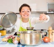 愉快的主妇用肉在厨房用桌上 免版税图库摄影