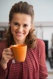 愉快的年轻主妇饮用的茶在厨房里 免版税库存图片