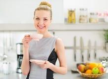 愉快的主妇饮用的茶在现代厨房里 库存照片