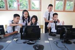 愉快的年轻学生是学习的互联网通讯技术聚集在教室 库存图片