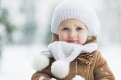 愉快的婴孩画象在冬天公园 免版税库存图片