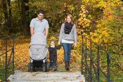愉快的年轻家庭在一起做徒步游览的秋天 免版税库存照片