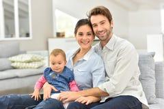愉快的年轻家庭在家坐沙发 库存图片