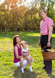 愉快的年轻家庭有野餐在草甸 免版税库存照片