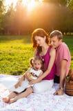 愉快的年轻家庭有野餐在草甸 图库摄影