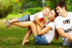 愉快的年轻家庭获得乐趣在绿色夏天公园outdoo 库存图片