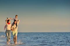 愉快的年轻家庭获得在跑的海滩的乐趣并且跳在日落 免版税库存照片