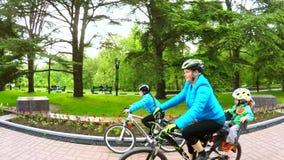 愉快的年轻家庭骑马自行车在绿园 股票录像