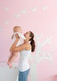 愉快的年轻从小儿床的母亲举的婴孩在家 免版税图库摄影