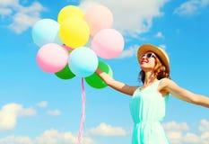 愉快的年轻微笑的妇女拿着五颜六色的气球获得穿在蓝天背景的乐趣一个夏天草帽的空气 免版税图库摄影