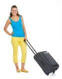 愉快的年轻旅游妇女全长画象有轮子袋子的 免版税图库摄影