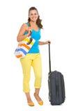 愉快的年轻旅游妇女全长画象有轮子袋子的 库存照片