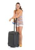 愉快的年轻旅游妇女全长画象有轮子袋子的 图库摄影