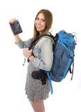 愉快的年轻显示护照的学生旅游妇女运载的背包在旅游业概念 免版税库存图片