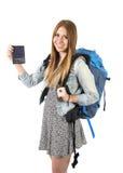 愉快的年轻显示护照的学生旅游妇女运载的背包在旅游业概念 免版税库存照片