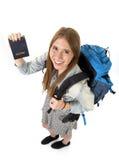 愉快的年轻显示护照的学生旅游妇女运载的背包在旅游业概念 图库摄影