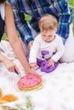 愉快的年轻有他们的小女儿的放松在一条毯子在公园庆祝与生日蛋糕的母亲和父亲 库存照片