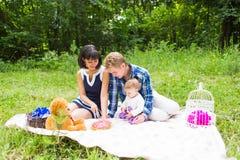 愉快的年轻有他们的小女儿的放松在一条毯子在公园庆祝与生日蛋糕的母亲和父亲 库存图片