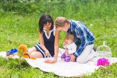愉快的年轻有他们的小女儿的放松在一条毯子在公园庆祝与生日蛋糕的母亲和父亲 免版税库存图片