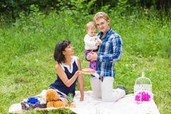 愉快的年轻有他们的小女儿的放松在一条毯子在公园庆祝与生日蛋糕的母亲和父亲 免版税库存照片