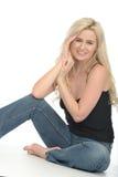 愉快的轻松的可爱的少妇坐看起来的地板喜欢 库存图片