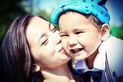 愉快的年轻母亲亲吻她的小儿子 图库摄影