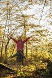 愉快的年轻母亲和她的小孩儿子投掷的秋叶喂 库存图片