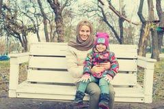 愉快的年轻母亲和小女儿在摇摆乘坐 免版税库存照片