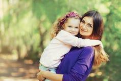 愉快的年轻母亲和逗人喜爱的孩子画象户外 免版税库存照片