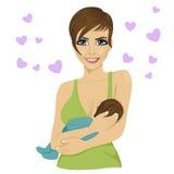 愉快的年轻母亲哺养的乳房她的白色背景的婴孩与心脏 免版税库存照片