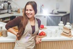 愉快的年轻深色的主妇在厨房里 库存照片