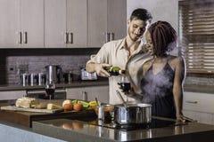 愉快的年轻烹调晚餐的混合的族种夫妇饮用的酒在厨房里 图库摄影
