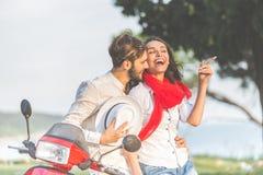 愉快的年轻爱夫妇画象在开心的滑行车的在公园在夏时 免版税库存照片