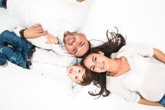 愉快的年轻父亲,母亲和逗人喜爱男婴说谎 库存照片