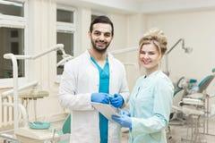 愉快的年轻医生和女性助理画象有片剂的在牙齿诊所 库存照片