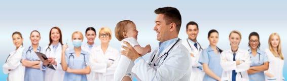 愉快的医生或儿科医生有婴孩的在蓝色 免版税库存照片