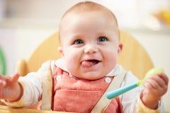 愉快的年轻男婴画象高脚椅子的 库存图片