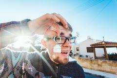 愉快的滑稽的人把握在房子被塑造的keychain的房子关键在一个新的家前面 免版税库存图片