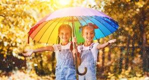 愉快的滑稽的姐妹在秋天孪生儿童女孩与伞 免版税库存图片